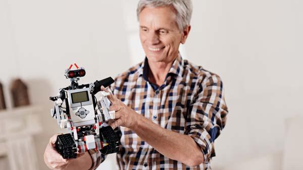 Sénior qui manipule un robot LEGO® Mindstorms