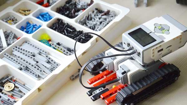 Robot LEGO® MIndstorms à côté de sa boite de pièces