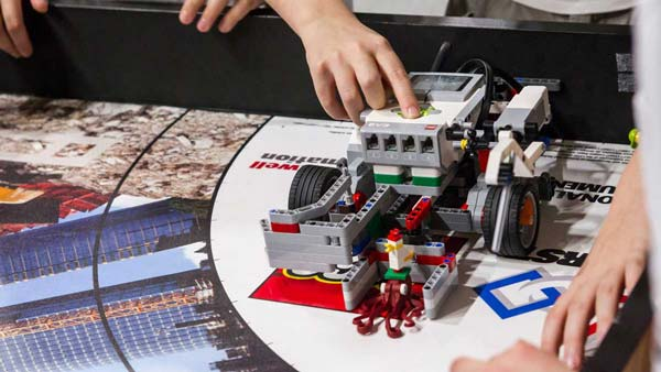 Robot LEGO® Mindstorms sur un tapis de compétition à la FIRST LEGO League en train d'être mis en route