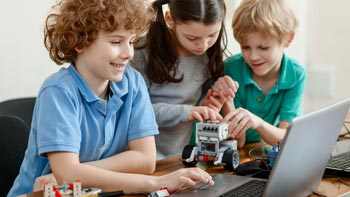 Apprendre l'informatique. Photo d'adolescents devant un ordinateur en train de programmer leur robot LEGO® Mindstorms