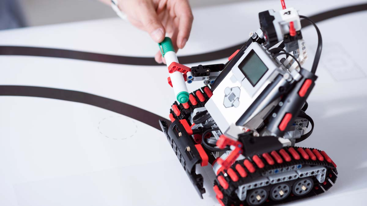 Robot LEGO® Mindstorms mi véhicule mi-humanoïde auquel une main humaine tend un stylo