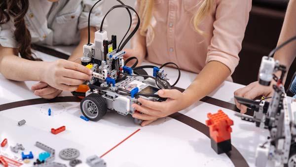 Enfants qui manipulent des LEGO® Mindstorms sur un tapis spécial à un cours de programmation robotique