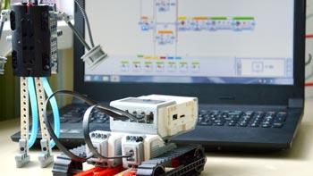 Apprendre à programmer. Photo d'un robot devant un ordinateur où est ouvert le logiciel de programmation LEGO® Mindstorms