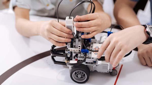 Mains d'adolescents en train de collaborer aux réglages d'un robot sur un tapis spécial